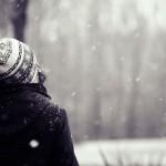 Девушка в парке на фоне падающего снега